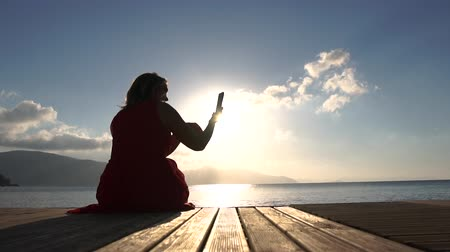 pontão : A woman sitting by the sea, taking pictures of a view at sunrise in slow motion