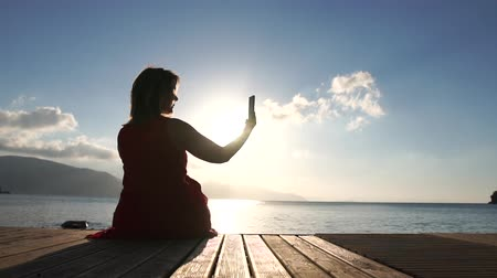 pontão : A woman takes pictures of a beautiful seascape on the phone in slow motion