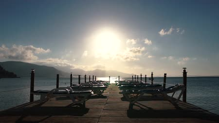 çare : Pontoon with empty sun loungers by the sea at sunrise in slow motion