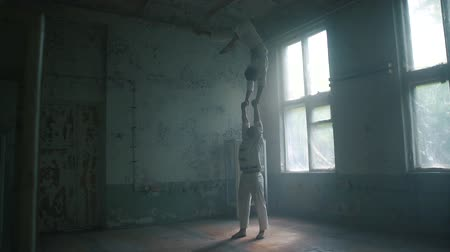 sağlam : One strong man standing and the second doing bent back handstand in hall in slo-mo Stok Video