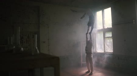 yıkık : One hardy man standing and the second doing bent back handstand in room in slo-mo
