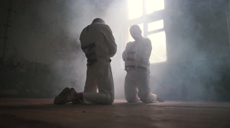 освещенный : Two crazy men kneeling against each other, looking aside in mental hospital in slo-mo