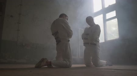 ajoelhado : Two wack men kneeling against each other, looking aside in mental house in slo-mo Vídeos