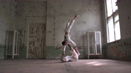 psycho : Two kook men doing a handstand with one lying down in a tacky hall