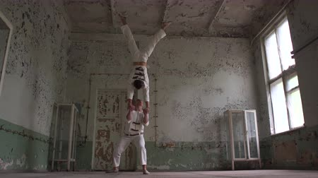 roto : Two psycho men doing a handstand together in a shabby hall Stock Footage