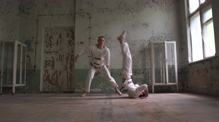roto : Two psycho men in white uniforms wrestling and falling in a shabby hall