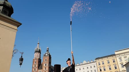 クラクフ : Cheery man standing and keeping a long tube with fireworks in Krakow in summer
