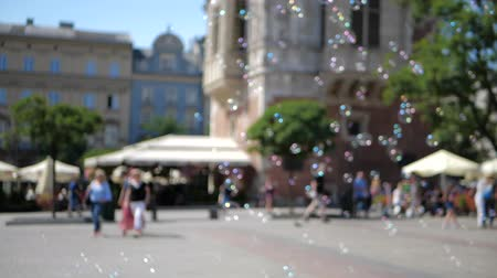 optimistický : Hilarious soap bubbles are flying low among people in Krakow square in summer