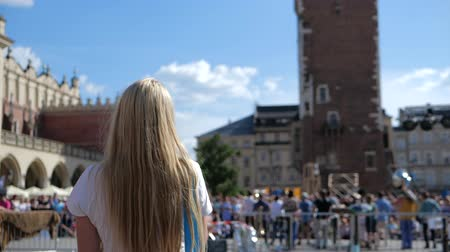 cracovie : Cheery blonde girl going and eating ice cream in Krakow in summer in slo-mo Vidéos Libres De Droits