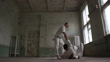 psycho : Two psycho men jumping and dancing breakdance together in a ragged room in slo-mo