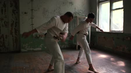 yıkık : Two psycho men dancing actively doing lunges and turning around in hall in slo-mo