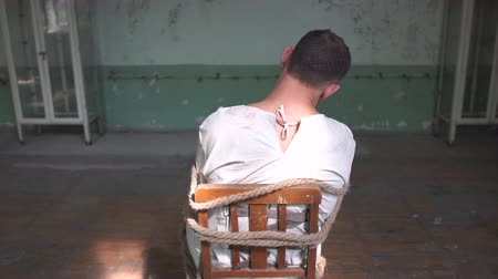 rundown : One kook man sitting being tied to a chair in shabby room Stock Footage