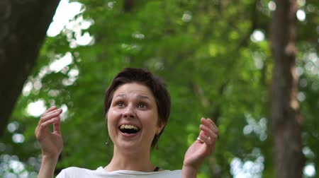 オリエンテーション : Happy young brunette woman laughing cheerily in a green wood in summer in slo-mo