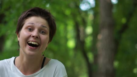 perfurante : Cheery young brunette woman laughing and keeping her head in hands in wood in slo-mo