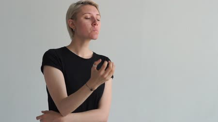 bastante : Elegant young blonde woman sitting and meditating in a white studio in slo-mo