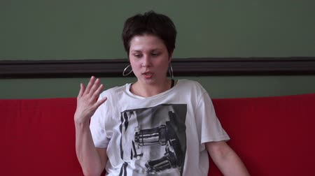 delici : Confident young woman sitting on a sofa and talking about her life in a studio in slo-mo