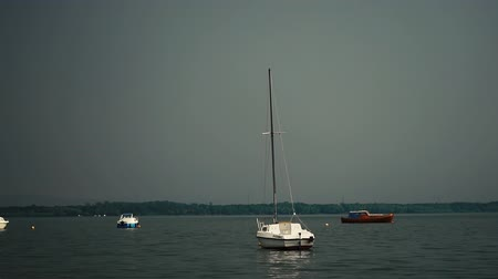 small vessels : A small yacht sways on the surface of the water in cloudy weather.