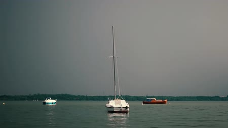 námořní loď : A small yacht sways on the surface of the water in cloudy weather.