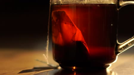 未使用 : Black tea is brewed from a tea bag, stands on a table in the morning sun.