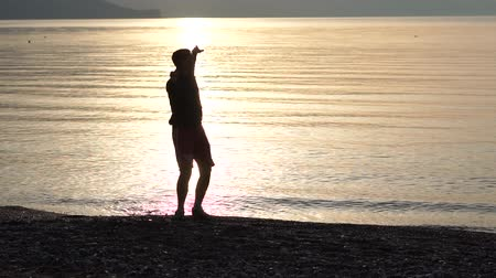 dab : Young man dancing on the seashore at sunrise in slow motion