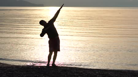 dab : The guy making dab arms gesture on the background of the sea in slow motion
