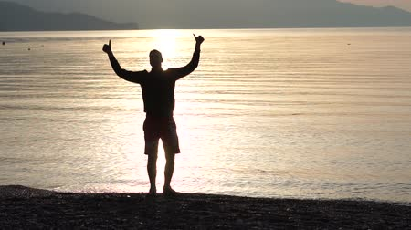 compleição : The boy doing positive gesture with hand, thumbs up on the background of the sea