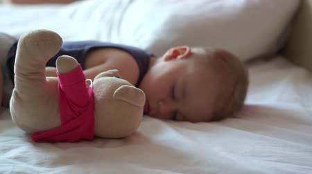 плюшевый мишка : Cute baby sleeps on the big bed with his beloved teddy bear in slow motion Стоковые видеозаписи