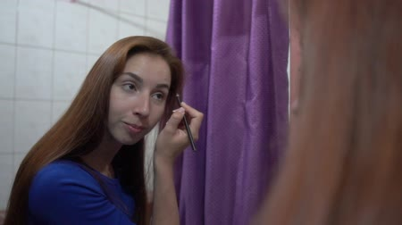 interessado : Beautiful brown hair girl putting makeup on her face before a mirror at home