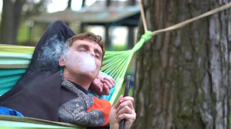 magánélet : Happy blond man lying on a braided hammock smoking hooka in summer in slo-mo Stock mozgókép