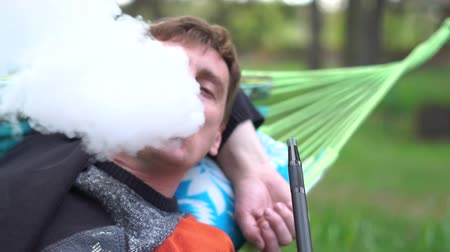 magánélet : Blissful blond man lying on a cane hammock smoking hooka in summer in slo-mo