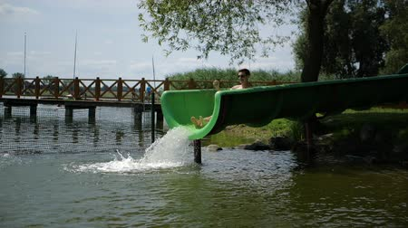 redhair : Young red-haired guy slides off a water slide into a lake in slow motion Stock Footage