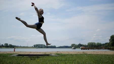 перемычка : Energetic joyful girl blonde beautifully jumps on a trampoline in nature