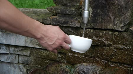 hidrasyon : Pouring water into a cup from a source in slow motion Stok Video