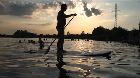 sucção : The silhouette of a man who on the beach of the lake swims on sup boat in slow motion.