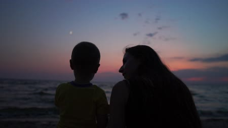 травянистый : Cheery mother sitting with her kid on sea shore at colorful sunset in slo-mo