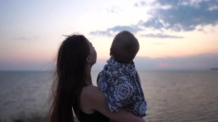 травянистый : Mother and little kid on her hands at sunset near the sea. Стоковые видеозаписи