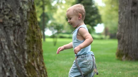 скрывать : Little cute boy runs in the park for his mom in slow motion Стоковые видеозаписи