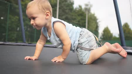 vigorous : Small cute boy crawls on all fours on a trampoline in slow motion