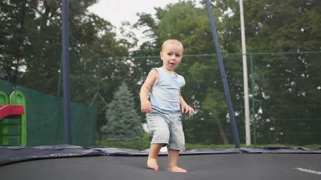 ugró : Little blond boy jumping on a trampoline in the park in slow motion