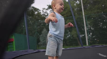 ugró : A small boy diligently jumps on a closed trampoline in the park in slow motion Stock mozgókép