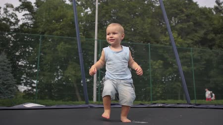 ugró : Little blond boy learns to jump on a trampoline in a park in slow motion