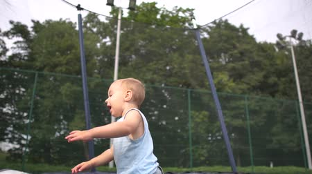 ugró : Smiling blond kid jumping falls on a trampoline in slow motion