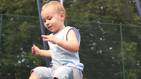 перемычка : Smiling boy jumping falls on a trampoline in slow motion