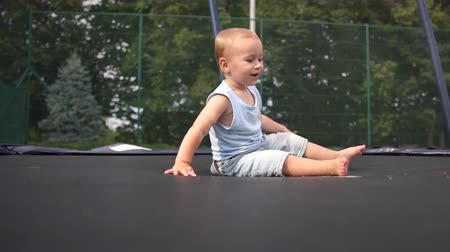 svetr : Joyful small boy jumping falls on a trampoline in slow motion Dostupné videozáznamy