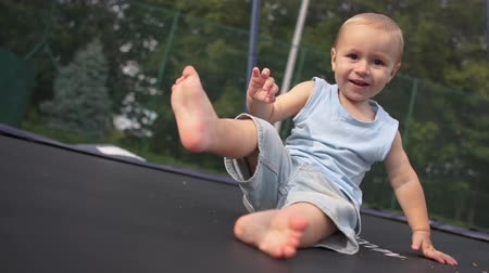 ugró : Cute smiling baby bounces and falls into a sitting position on a trampoline. Stock mozgókép