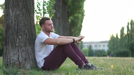 cheerless : Lonely guy sits and sad under a tree in slow motion