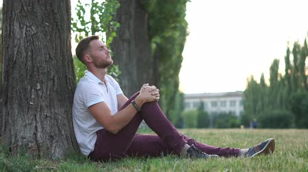 cheerless : Sad guy sitting in a park under a tree in slow motion