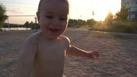 little funny boy in swimming trunks runs and waves his hands at the camera - slow motion.