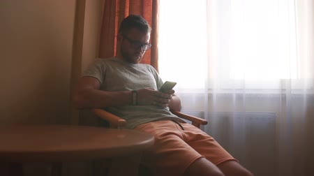 A man sits on a chair near a window in a hotel room and works with a telephone.