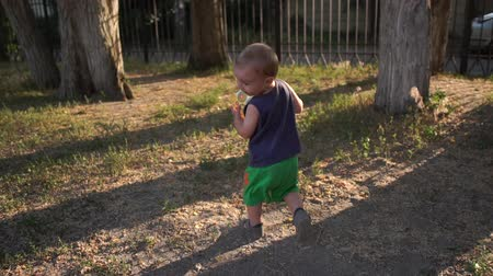 Little boy runs with the ball in his hands and laughs slow motion.
